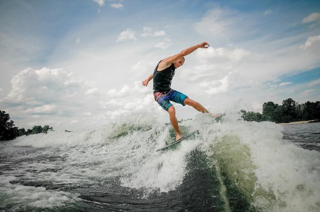 Een jonge surfer die de golf op een surfplank berijdt