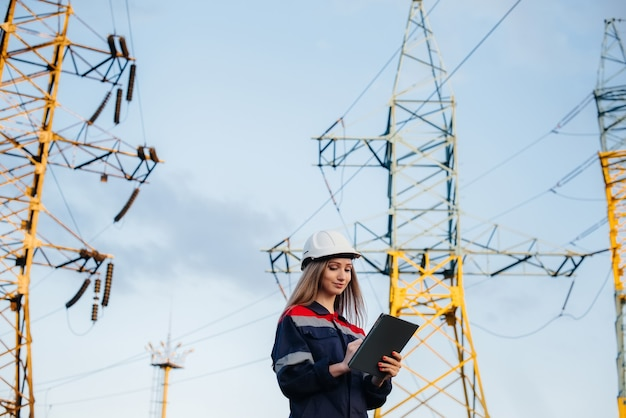Een jonge technische werknemer inspecteert en controleert de uitrusting van de hoogspanningslijn. energie.