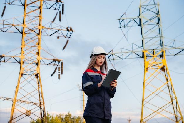 Een jonge technische werknemer inspecteert en controleert de uitrusting van de hoogspanningslijn