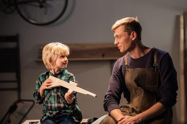 Een jonge timmermansvader en zijn schattige blonde zoon maakten een geweer van hout en laten het zien, ze zijn blij, zittend in de timmermanswerkplaats op de tafel.
