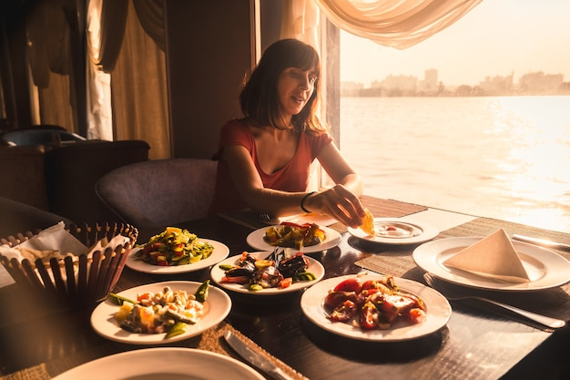 Een jonge toerist aan het dineren op een boot op de nijl
