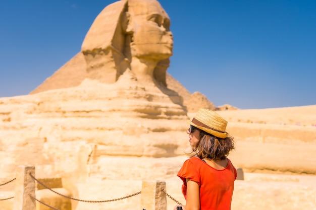 Een jonge toerist bij de grote sfinx van gizeh, gekleed in het rood en met een hoed, vanwaar de miramides van gizeh. caïro, egypte