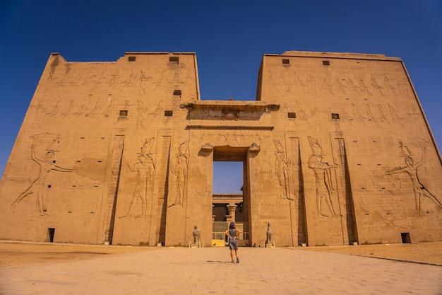 Een jonge toerist bij de ingang van de edfu-tempel bij de rivier de nijl in aswan. egyptische