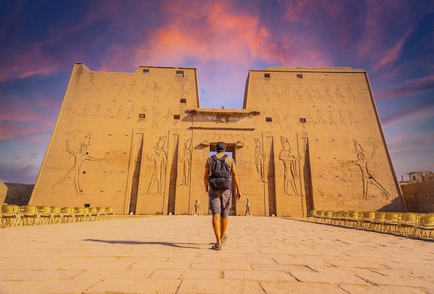 Een jonge toerist die de tempel van edfu in de stad edfu binnengaat bij zonsondergang, egypte. aan de oevers van de rivier de nijl, geco-romeinse constructie, tempel gewijd aan huros