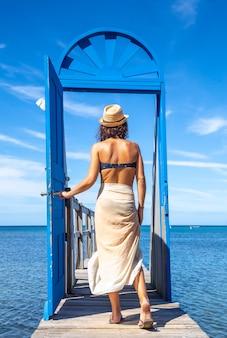 Een jonge toerist die door de blauwe deur op een houten loopbrug op het caraïbische eiland roatan in honduras loopt, verticale foto