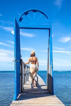 Een jonge toerist die door de blauwe deur op een houten wandelpad op het caraïbische eiland roatan in honduras loopt