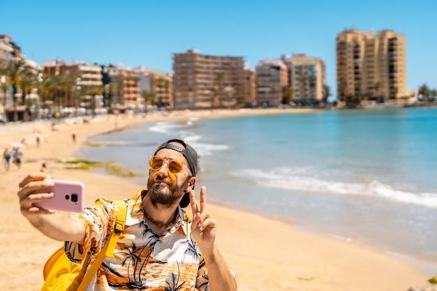 Een jonge toerist die een selfie maakt bij playa del cura in de kustplaats torrevieja, alicante, valenciaanse gemeenschap