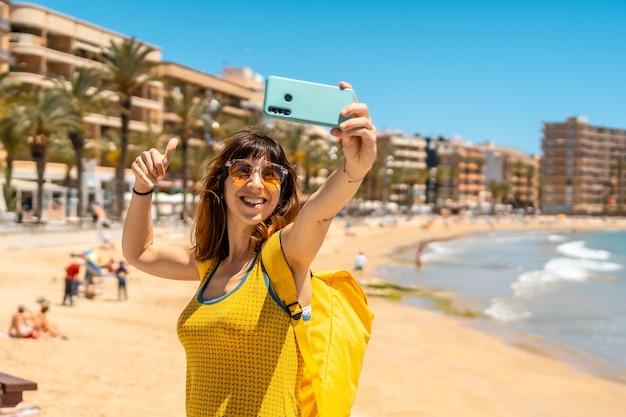 Een jonge toerist die een selfie maakt met de telefoon op playa del cura in de kustplaats torrevieja, alicante, valenciaanse gemeenschap
