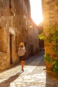 Een jonge toerist die in de middeleeuwse stad pals loopt, straten van het historische centrum bij zonsondergang, girona aan de costa brava van catalonië in de middellandse zee