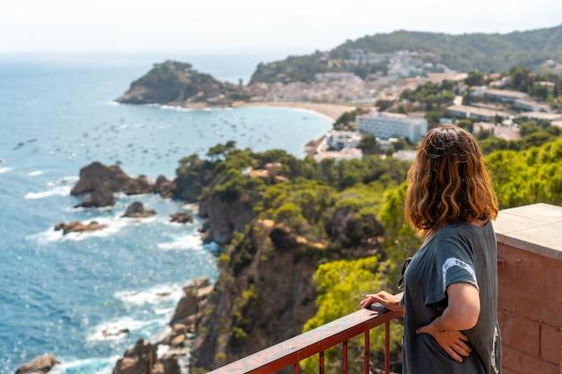 Een jonge toerist die in de zomer vanuit het gezichtspunt naar tossa de mar kijkt, girona aan de costa brava van catalonië in de middellandse zee