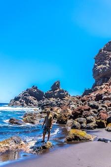 Een jonge toerist geniet van de zomer aan zee op een aantal rotsen in playa de nogales in het oosten van het eiland la plama, canarische eilanden. spanje