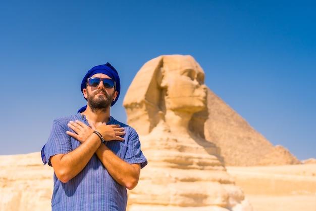 Een jonge toerist in de buurt van de grote sfinx van gizeh, gekleed in blauw en een blauwe tulband, vanwaar de miramides van gizeh. caïro, egypte