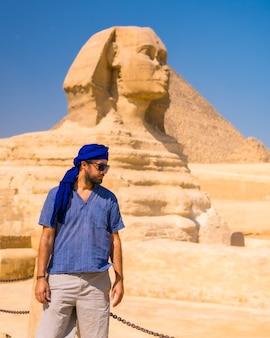 Een jonge toerist in de buurt van de grote sfinx van gizeh gekleed in het blauw en een blauwe tulband, van waaruit de miramides van gizeh, cultureel toerisme en veel geschiedenis. caïro, egypte