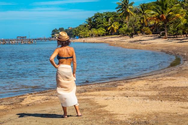 Een jonge toerist in een bikini en rok op het strand van sandy bay op roatan island. honduras