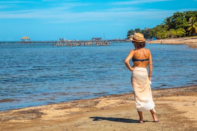 Een jonge toerist in een bikini en rok op het strand van sandy bay op roatan island kijken naar de caribische zee. honduras