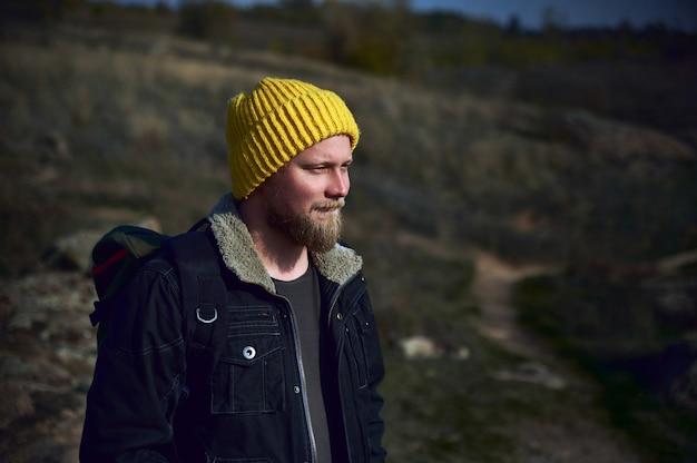 Een jonge toerist in gele hoed en een rugzak die zich op de loopbrug van de berg bevinden. reizen, avontuur, natuur, vrijheid concept.
