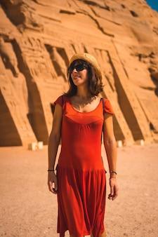 Een jonge toerist in rode jurk die de tempel van nefertari bezoekt bij abu simbel in het zuiden van egypte in nubië naast het nassermeer. tempel van farao ramses ii, reislevensstijl