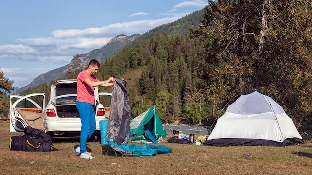 Een jonge toerist is bezig met het verzamelen van spullen, het inpakken van een slaapzak op een camping, op de achtergrond een tent en een auto. het concept van recreatie en toerisme in de bergen met de auto