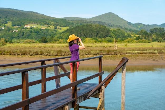 Een jonge toerist kijkt met een verrekijker naar vogels vanaf de houten pieren van de urdaibai-moerassen, een biosfeerreservaat in bizkaia naast mundaka. baskenland