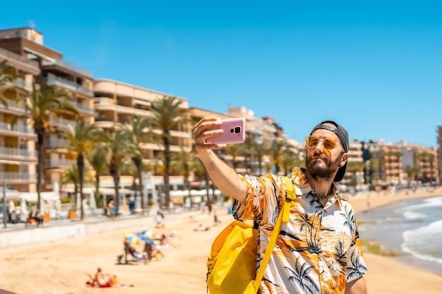 Een jonge toerist met de telefoon op playa del cura in de kustplaats torrevieja, alicante, valenciaanse gemeenschap