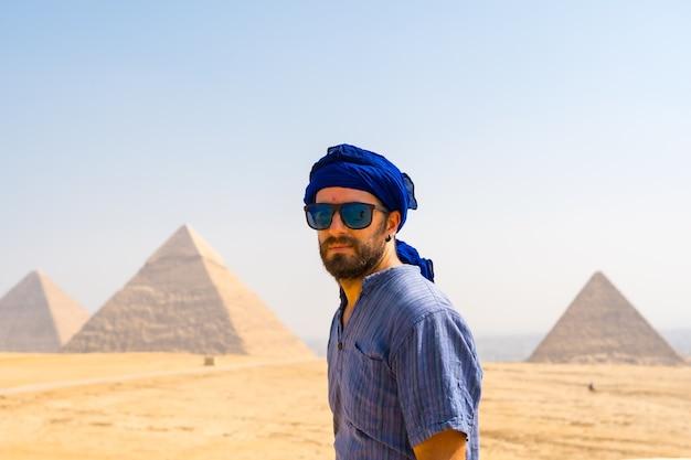 Een jonge toerist met een blauwe tulband en een zonnebril genietend van de piramides van gizeh, het oudste grafmonument ter wereld. in de stad caïro, egypte
