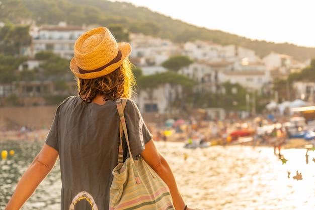 Een jonge toerist met een hoed bij zonsondergang aan de kust van tamariu in de stad palafrugell. girona, costa brava in de middellandse zee