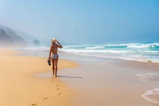Een jonge toerist met een hoed die alleen loopt op het cofete-strand van het natuurpark jandia, barlovento, ten zuiden van fuerteventura, canarische eilanden. spanje