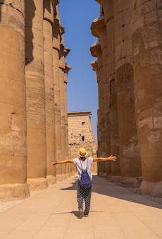 Een jonge toerist met een hoed die de egyptische tempel van luxor bezoekt