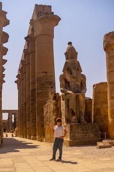 Een jonge toerist met een hoed die de egyptische tempel van luxor en zijn prachtige zuilen bezoekt