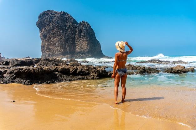 Een jonge toerist met een hoed in de roque del moro van het cofete-strand van het natuurpark jandia, barlovento, ten zuiden van fuerteventura, canarische eilanden. spanje