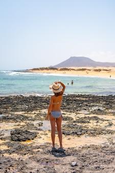 Een jonge toerist met een hoed op de stranden van het natuurpark corralejo met de zee op de achtergrond, fuerteventura, canarische eilanden. spanje