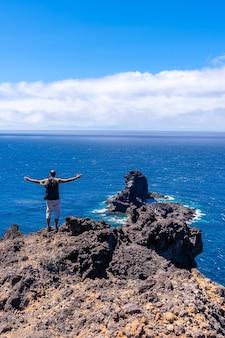 Een jonge toerist op het klifpad op de afdaling naar het zwarte zandstrand van bujaren, ten noorden van het eiland la palma, canarische eilanden. spanje
