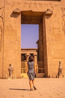 Een jonge toerist verlaat de edfu-tempel bij de rivier de nijl in aswan. egypte