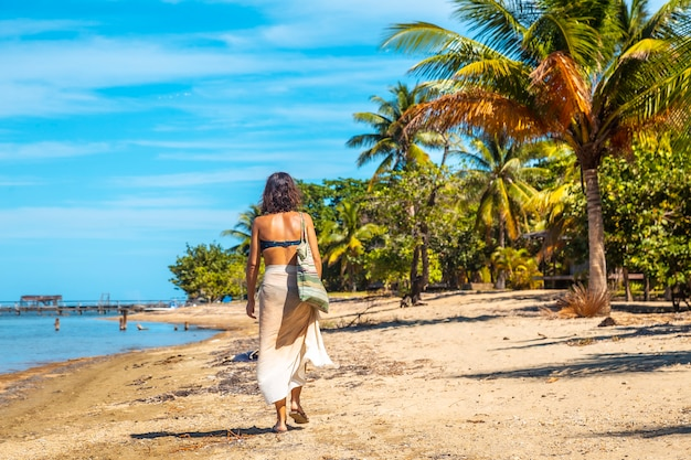 Een jonge toerist wandelen langs het strand van sandy bay op roatan island. honduras