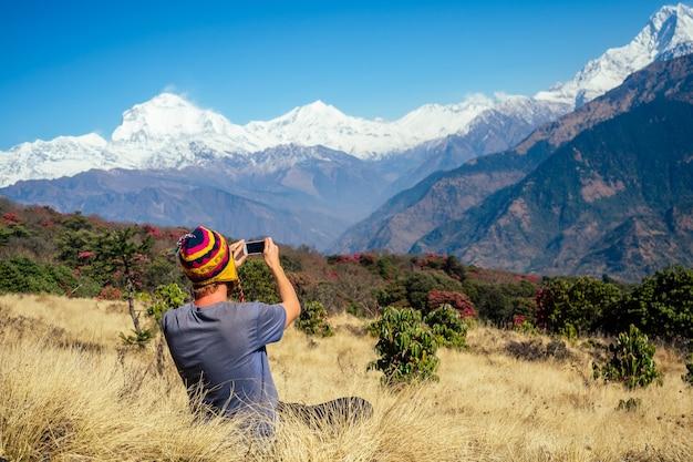 Een jonge toeristenman met een wandelrugzak en een gebreide muts die foto's maakt van de landschappen en selfies maakt in de himalaya-bergen. trekkingsconcept in de bergen.