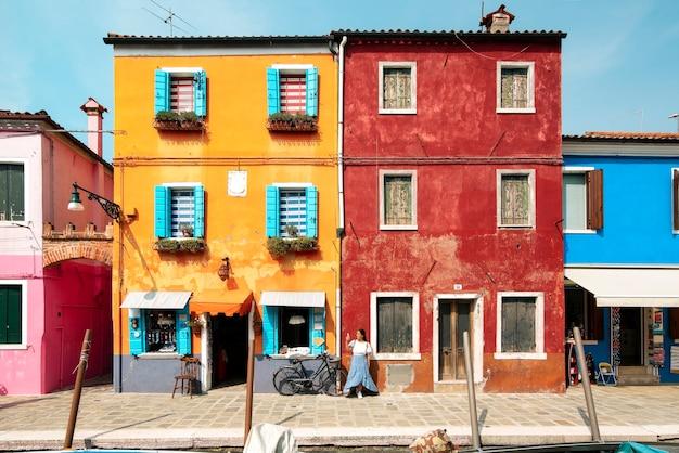 Een jonge toeristenvrouw in de kleurrijke straten van burano in venetië tijdens het glimlachen en een bezoek aan de italiaanse stad