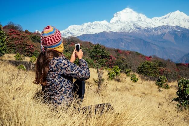 Een jonge toeristenvrouw met een wandelrugzak en een gebreide muts die foto's maakt van de landschappen en selfies maakt in de himalaya-bergen. trekkingconcept in de bergen