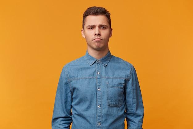 Een jonge trieste man staat met een sombere gezichtsuitdrukking verveeld boos, geïsoleerd tegen een gele muur
