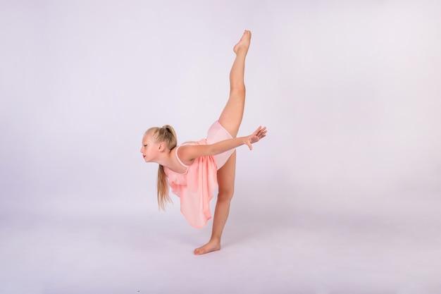 Een jonge turnster in een perzikzwempak staat in een gymnastiekhouding op een witte geïsoleerde muur