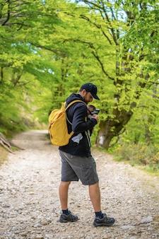 Een jonge vader die het pasgeboren kind goed in de rugzak stopt op een pad in het bos op weg naar de picknick met het gezin