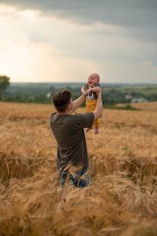 Een jonge vader houdt zijn drie maanden oude zoon in zijn armen. gefilmd in een tarweveld.