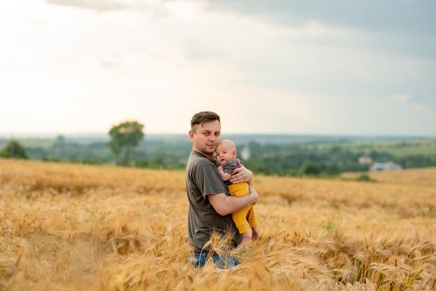 Een jonge vader houdt zijn drie maanden oude zoon in zijn armen.