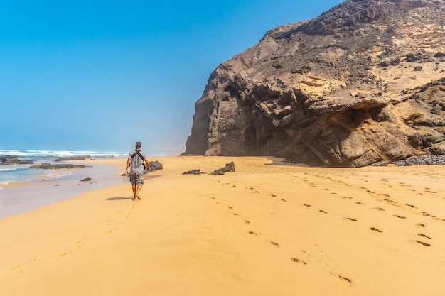Een jonge vader in de roque del moro van het cofete-strand van het natuurpark van jandia, barlovento, ten zuiden van fuerteventura, canarische eilanden. spanje