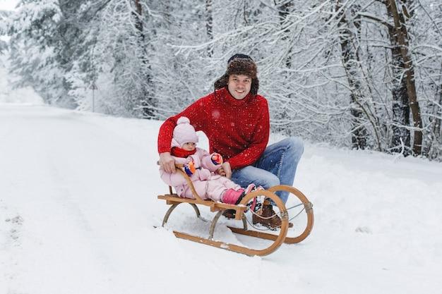 Een jonge vader in een rode trui rijdt met zijn charmante dochter op een houten slee in een besneeuwd bos.