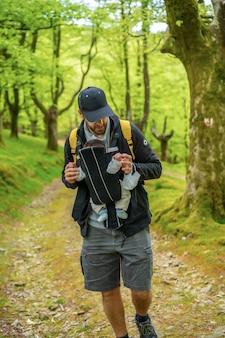 Een jonge vader met een gele rugzak loopt met het pasgeboren kind in de rugzak over een pad in het bos