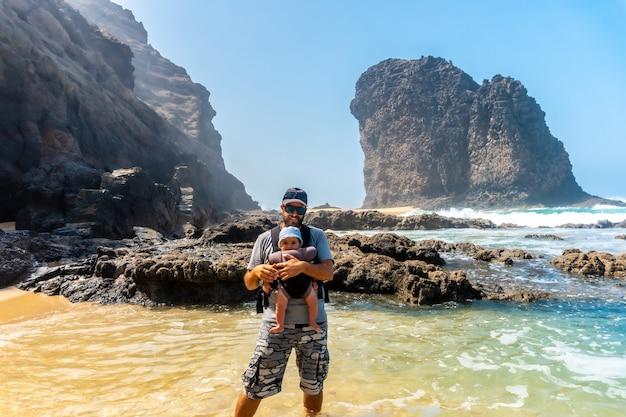Een jonge vader met zijn baby in zijn rugzak in de roque del moro van het cofete-strand van het natuurpark jandia, barlovento, ten zuiden van fuerteventura, canarische eilanden. spanje