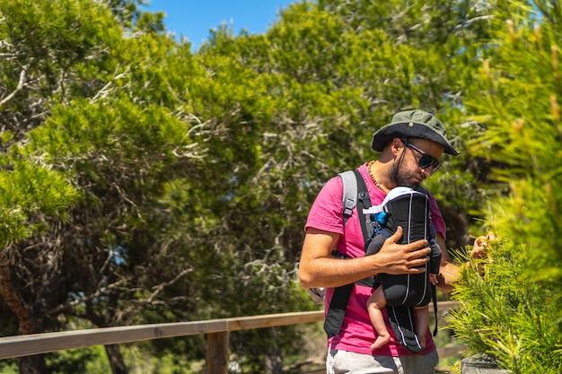 Een jonge vader met zijn zoon in zijn rugzak op weg naar playa moncayo in guardamar del segura naast torrevieja, alicante