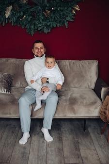Een jonge vader zit met zijn jonge kind op de bank