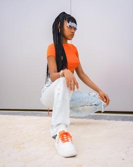 Een jonge valdanseres met vlechten. zwart etnisch meisje met oranje t-shirt en cowboybroek op een grijze achtergrond, in een stedelijke rapper-pose