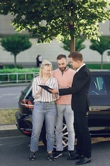 Een jonge verkoper laat klanten een nieuwe auto zien. gelukkig stel, man en vrouw kopen een nieuwe auto. jongeren ondertekenen documenten om een auto te kopen.